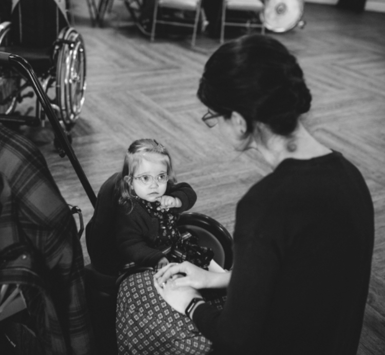 A small girl with Spina bifida and hydrocephalus sits with her mum.