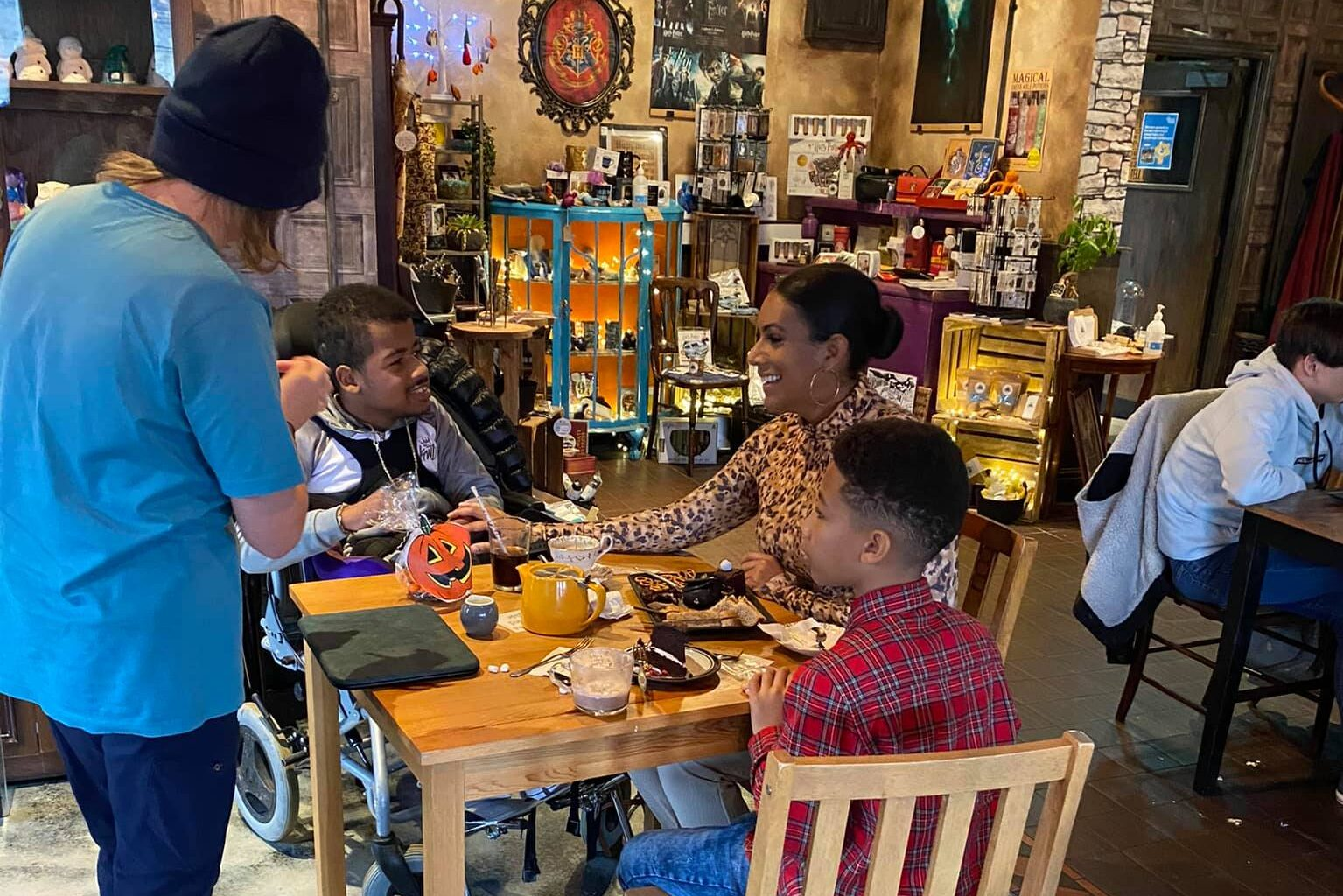 A family enjoys their refreshments in the cafe. A magician performs some tricks for entertainment.