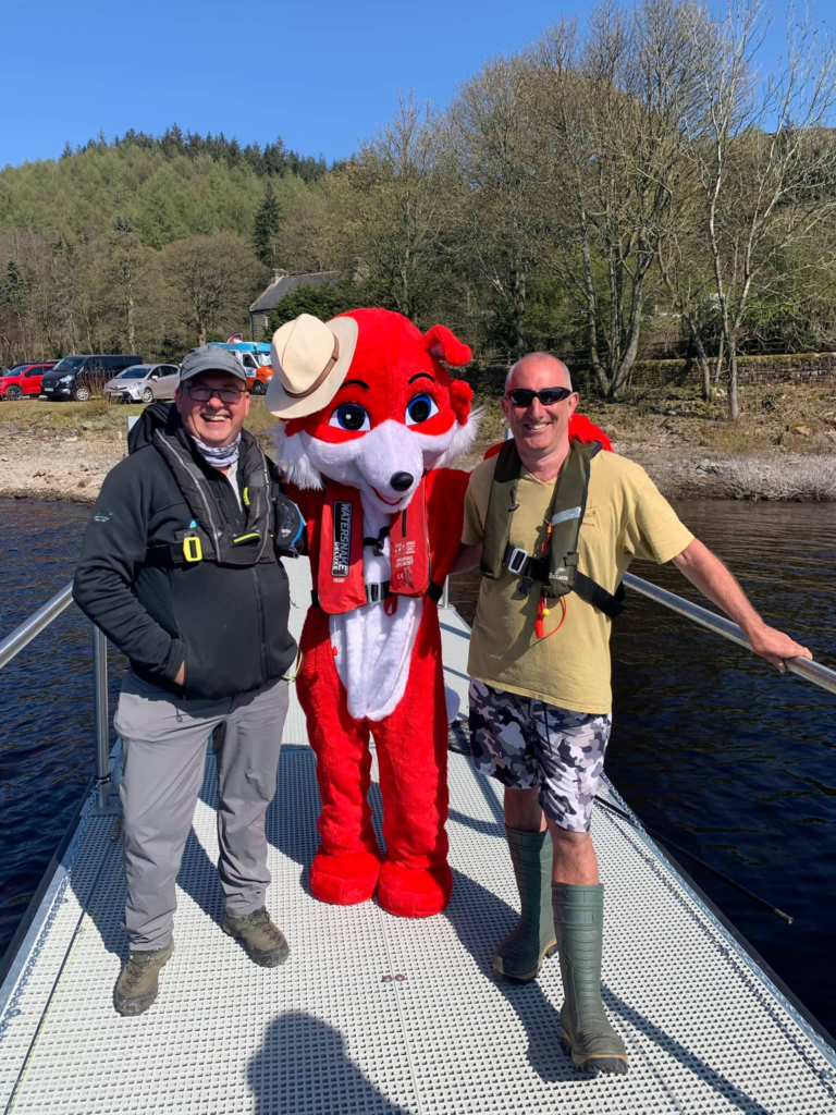 Shasby is a big red fox. He is posing on the accessible fishing pontoon with Richard and Troy from Ladybower Fisheries.