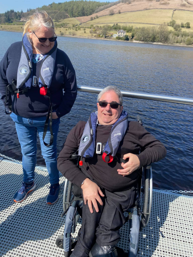 Two of our adult SHASBAH members smile for a photo on the accessible fishing pontoon.