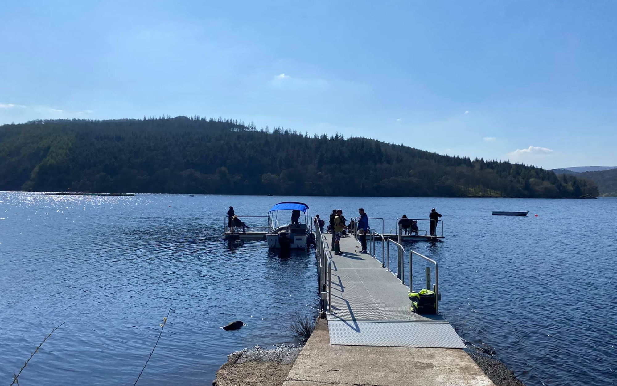 The accessible fishing pontoon on Ladybower Reservoir is surrounded by beautiful hills and trees.