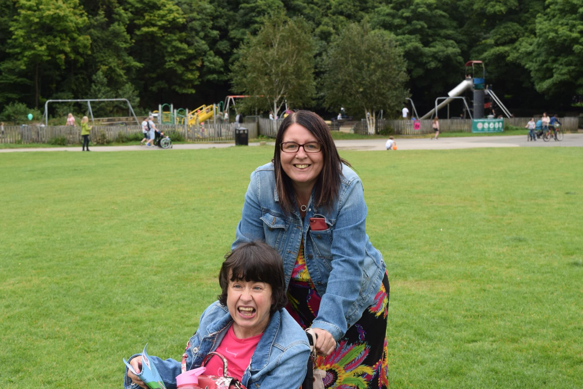 Two ladies smile for a photo in a park. The lady in the front is in a wheelchair. Both are wearing denim jackets.