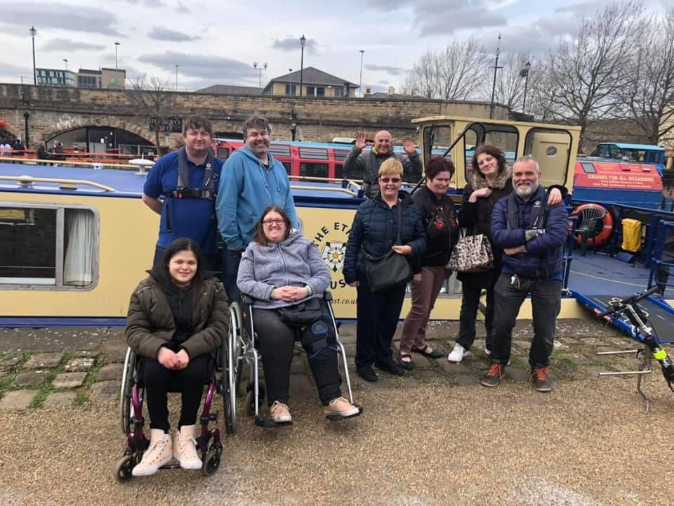 A group of people pose in front of an accessible canal boat. The group includes two wheelchair users.