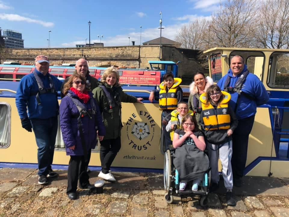 A group of people, one in a wheelchair and wearing yellow lifejackets, pose in front of a canal boat.