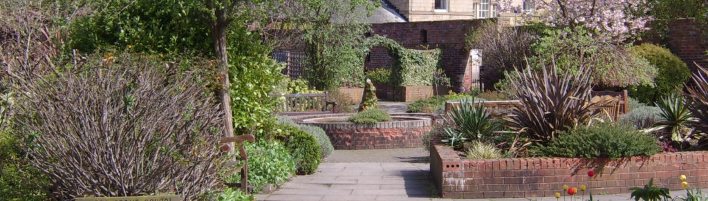 A photo looking down a path through Hillsborough Walled Garden. Plants are on either side and there is a fountain in the centre.