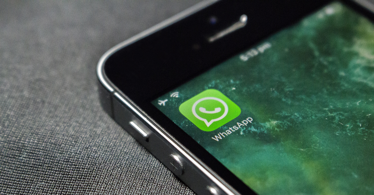 A Photo Of The Corner Of An IPhone Screen On A Grey Background. The Screen Shows The Green WhatsApp Icon In The Top Left Corner.