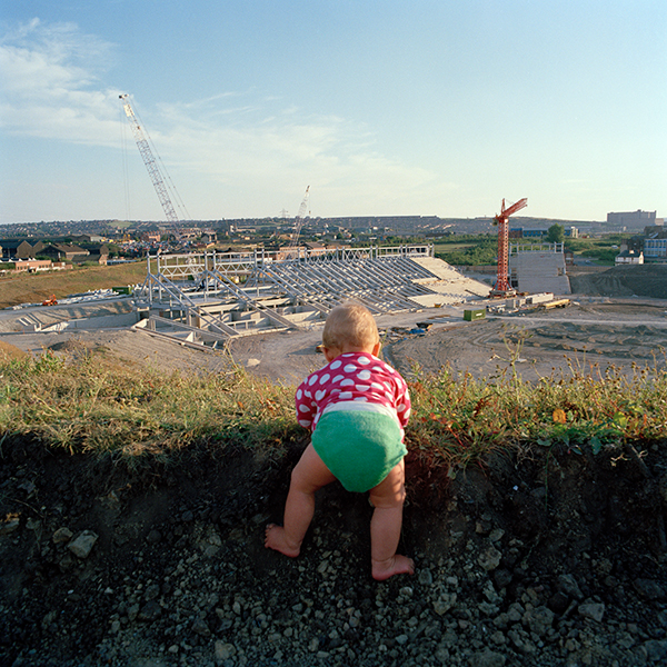 A baby climbs on a hedge, which over looks the building site of the Don Valley Stadium in Sheffield.